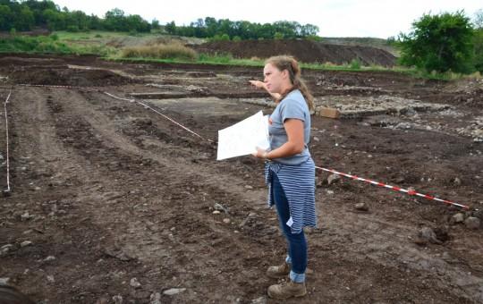 Marie-Caroline détaillant les fouilles d'une immense batisse, toujours en cours de fouille